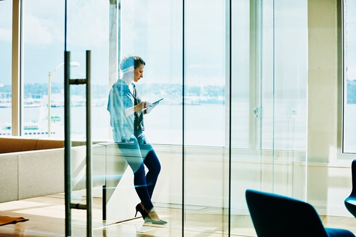 One individual in a meeting area checking device for information behind a glass wall