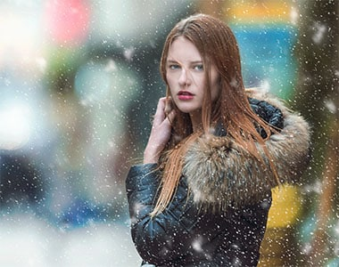 Woman standing in the street under snowy weather