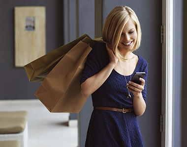 Woman carrying shopping bags while looking at smartphone