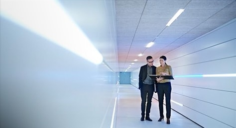 a man and a woman with a laptop in a hall