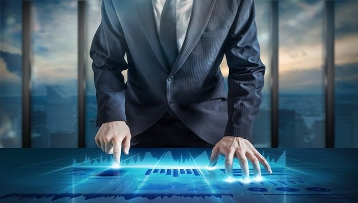 Man standing with hands on surreal, lighted desk with blue halo