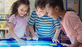Three children playing with interactive screen