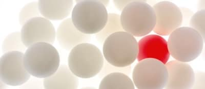 white balls against a light and one red ball among them