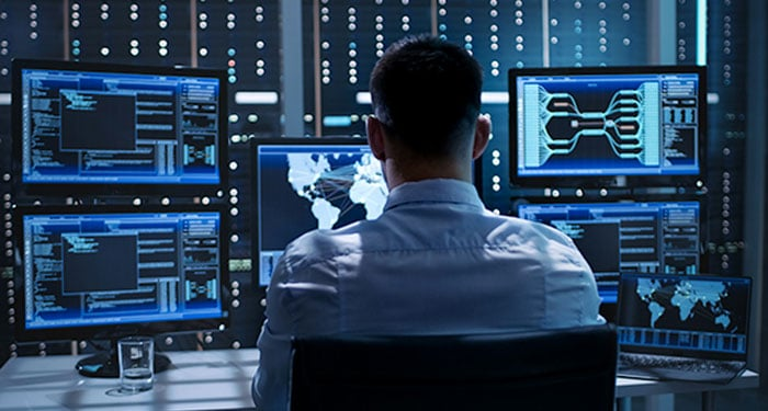 Man using multiple monitors in security operations center