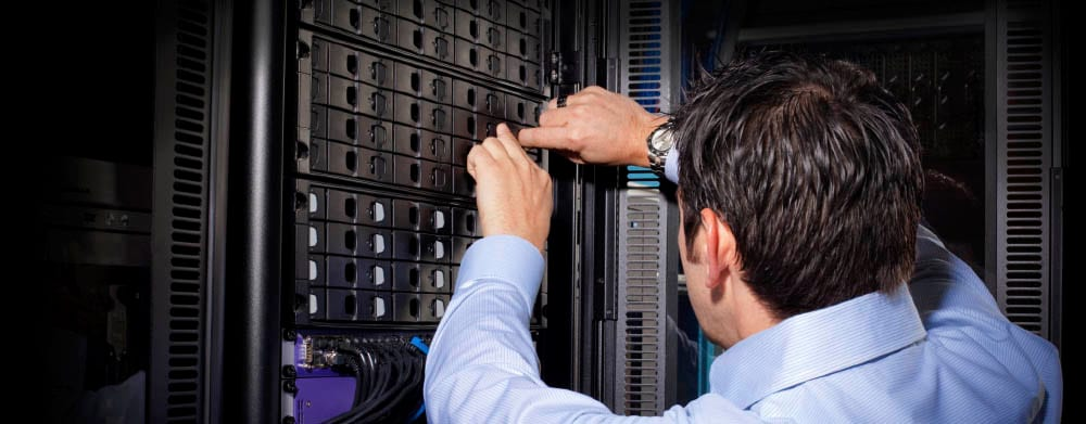 Generic photo of a man working on servers, representing use of Cloud Backup for server reconstruction