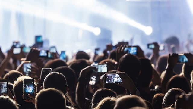 A sea of attendees at a performance, with many of them aiming smartphone cameras at the stage.