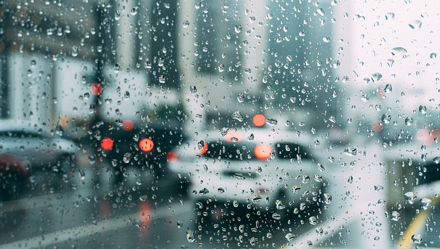 Rainy day traffic on city streets, as seen through a rain-spattered window.