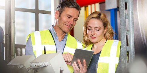 Man and woman in yellow safety vests reviewing maintenance records