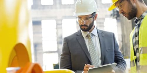 man on suit wearing helmet on side of worker inspecting equipment
