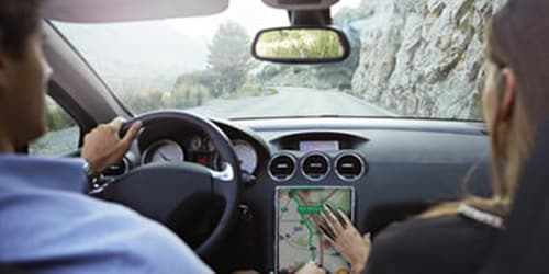couple driving a car, man on wheel, woman using big map touchscreen on car console