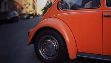 The back of a orange VW Beetle