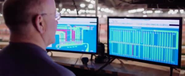 Man looking at graphs in a couple screens