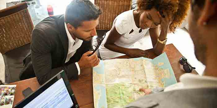 A couple in a travel agency looking at a map