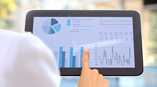 A tablet depicting an analytics solution with pie charts, bar graphs and statistics