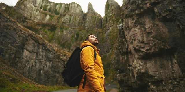 man in yellow jacket standing amongst tall stony mountains