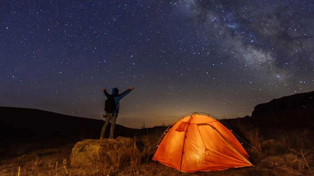 image of a man looking at milky way at night standing next to a tent