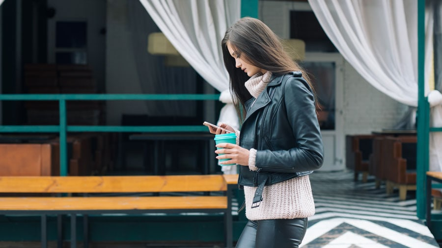 image of woman walking down street with phone in hand