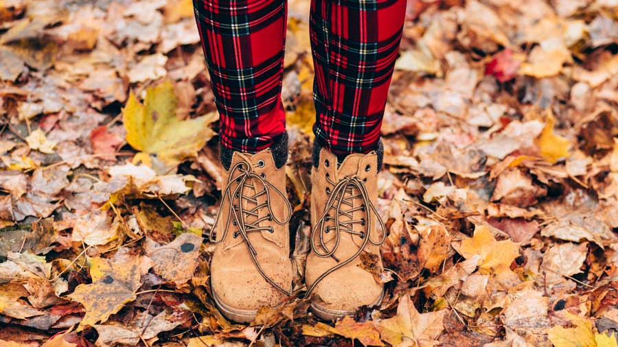 closeup of person's feet with boots on standing on top of autumn leaves