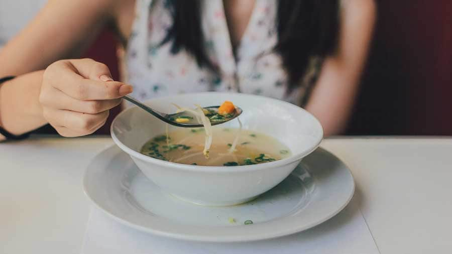 closeup of a soup bowl from a woman eating soup