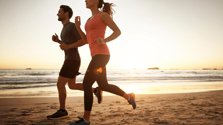 man and woman running together on the beach with sunset in the background