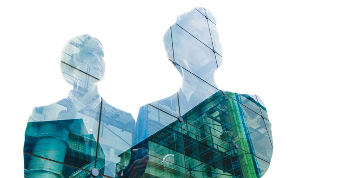 Glass building reflected in two human silhouettes