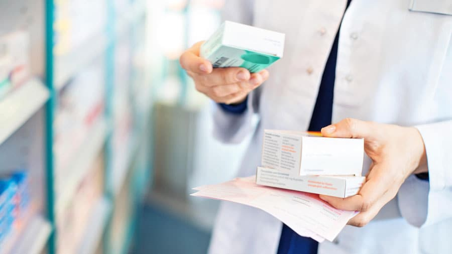pharmacist holding several boxes of medication in hand