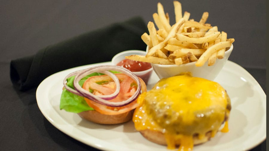 open face cheeseburger on a plate with lettuce tomato onion and fries