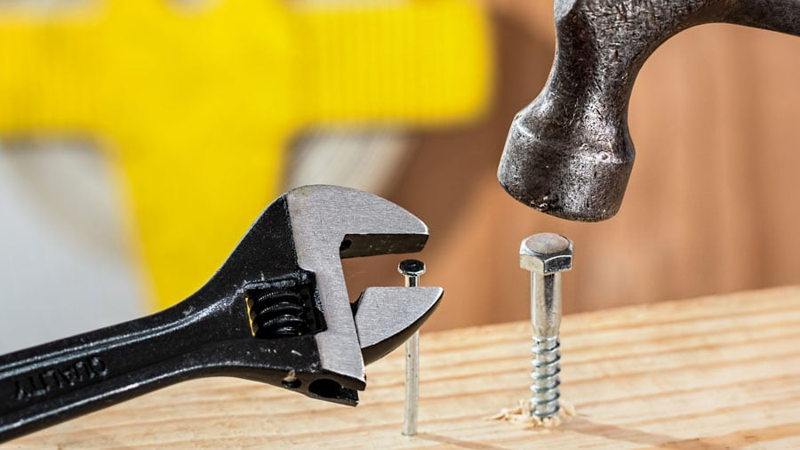 wrench and hammer beside a screw and nail protruding from a piece of wood
