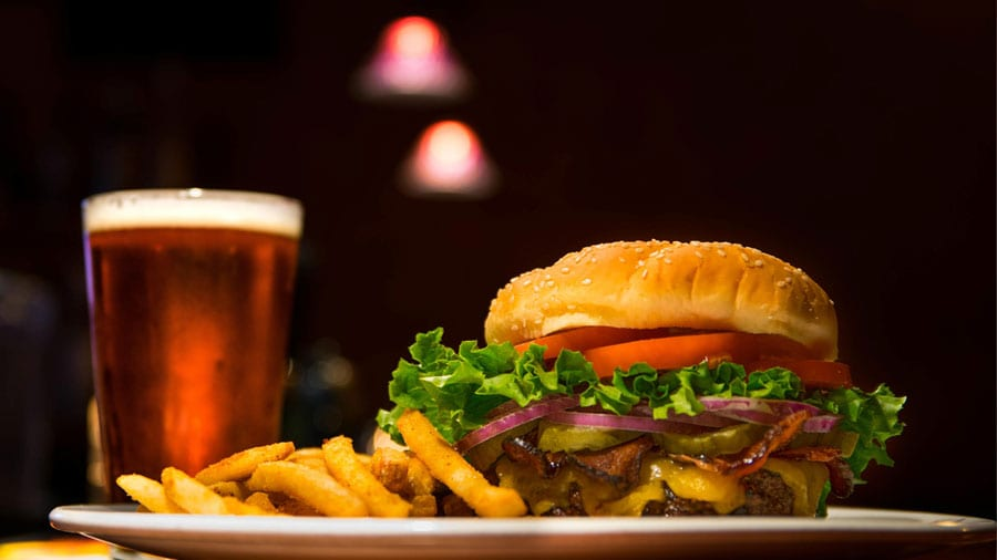 sideview closeup of a burger with fries and beverage in the background