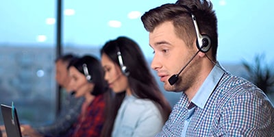 Four people working at an IT customer service desk