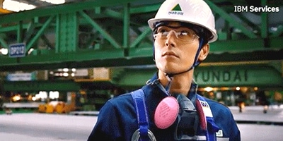 An industrial worker wearing safety gear standing in front of heavy machinery