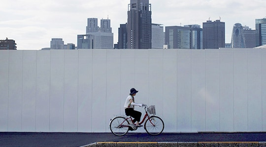 Woman riding bicycle in front of wall