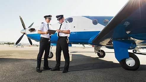 two pilots confer in front of a small, parked jet