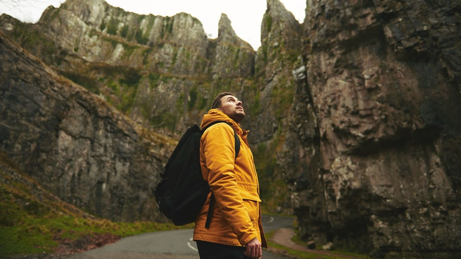 man in yellow jacket standing next to a mountain looking up at the view