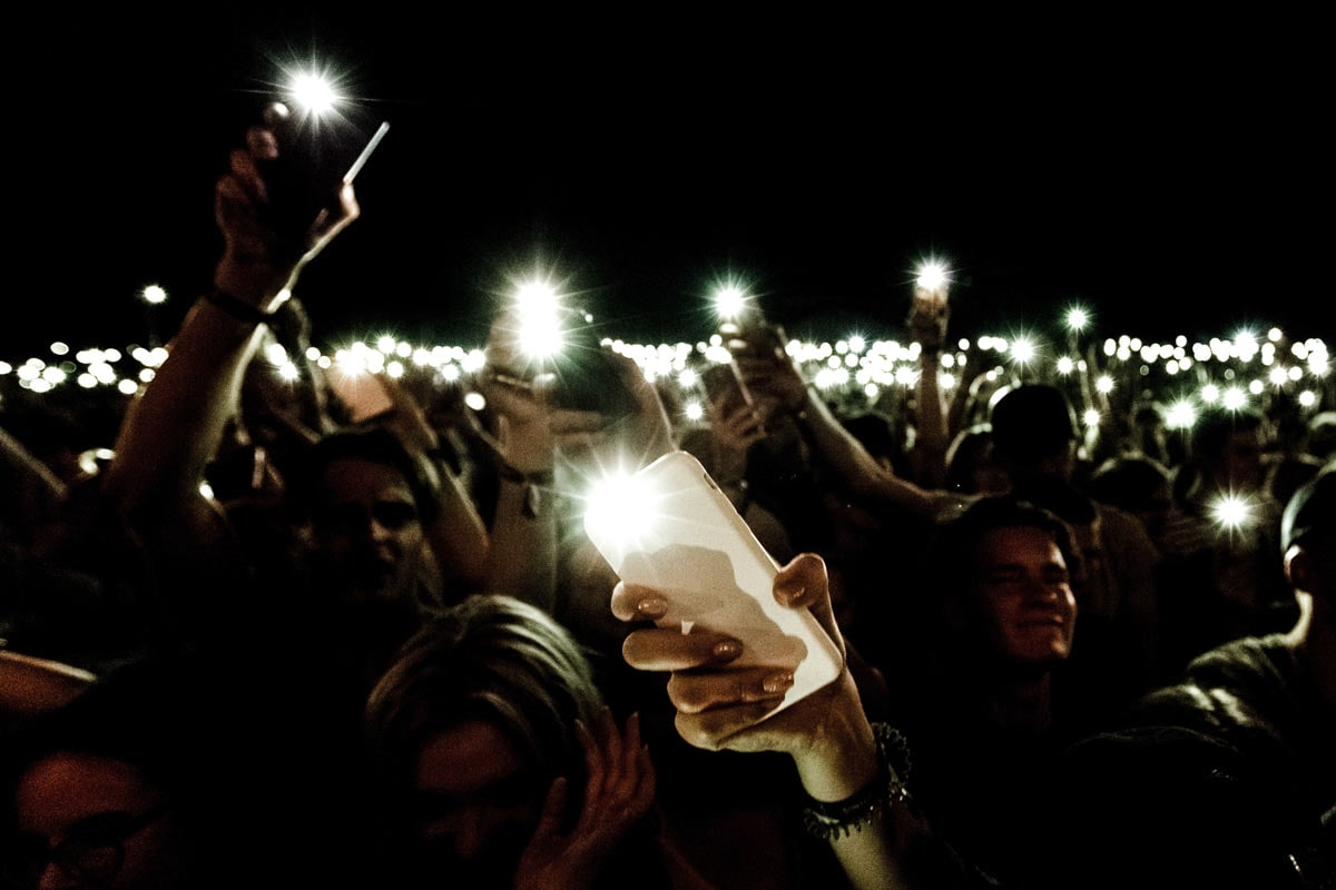 crowd all holding phones with flashlights on at night