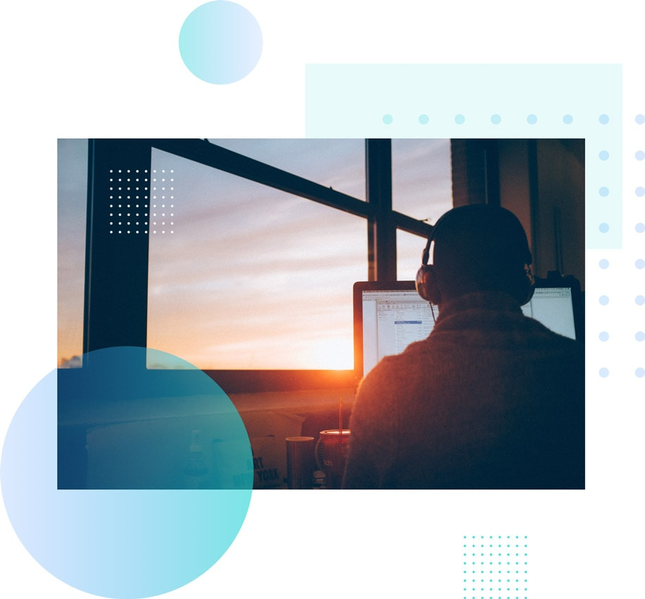 man sitting in front of a computer inside an office with a sunset outside