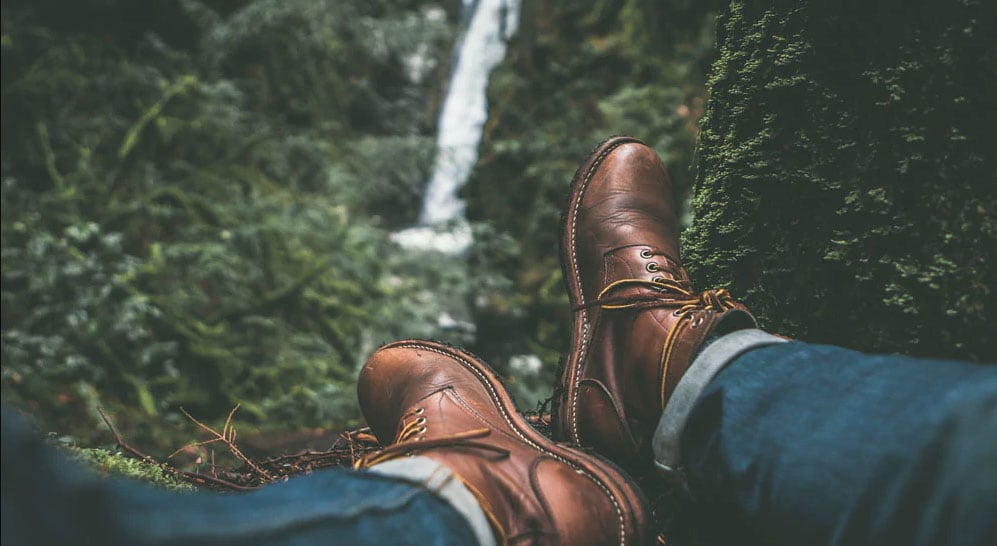 brown boots on a person overlooking a waterfall