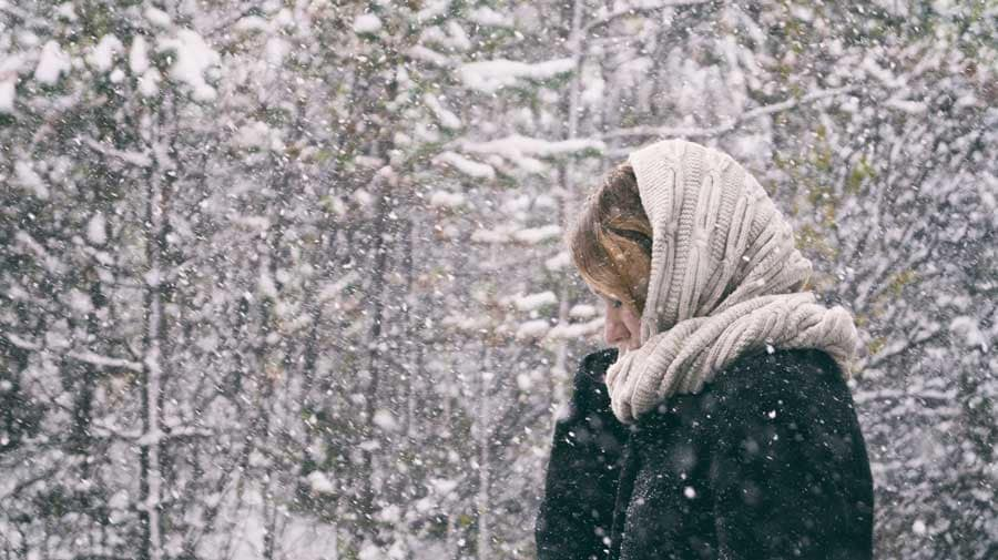 woman with beige knitted scarf around her head in the snow