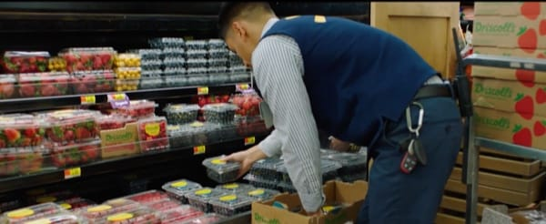 Supermarket employee replenishing food on a shelf