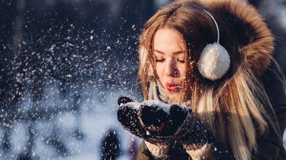 woman in black coat and ear muffs blowing snow from her hands