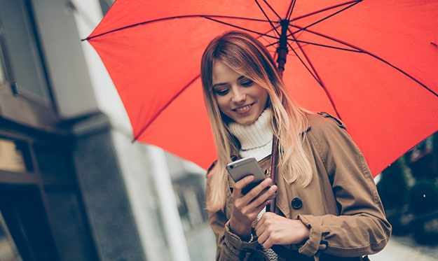 Woman looking at phone while carrying red umbrella