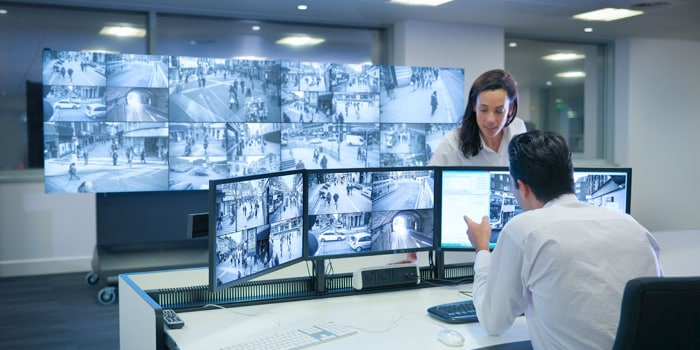 Two employees checking street security cameras monitors