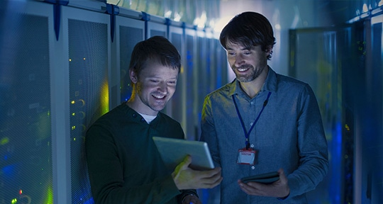 Photograph of two workers in data center testing early and often