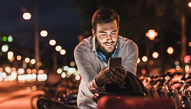Man looking at phone at night with city lights behind him