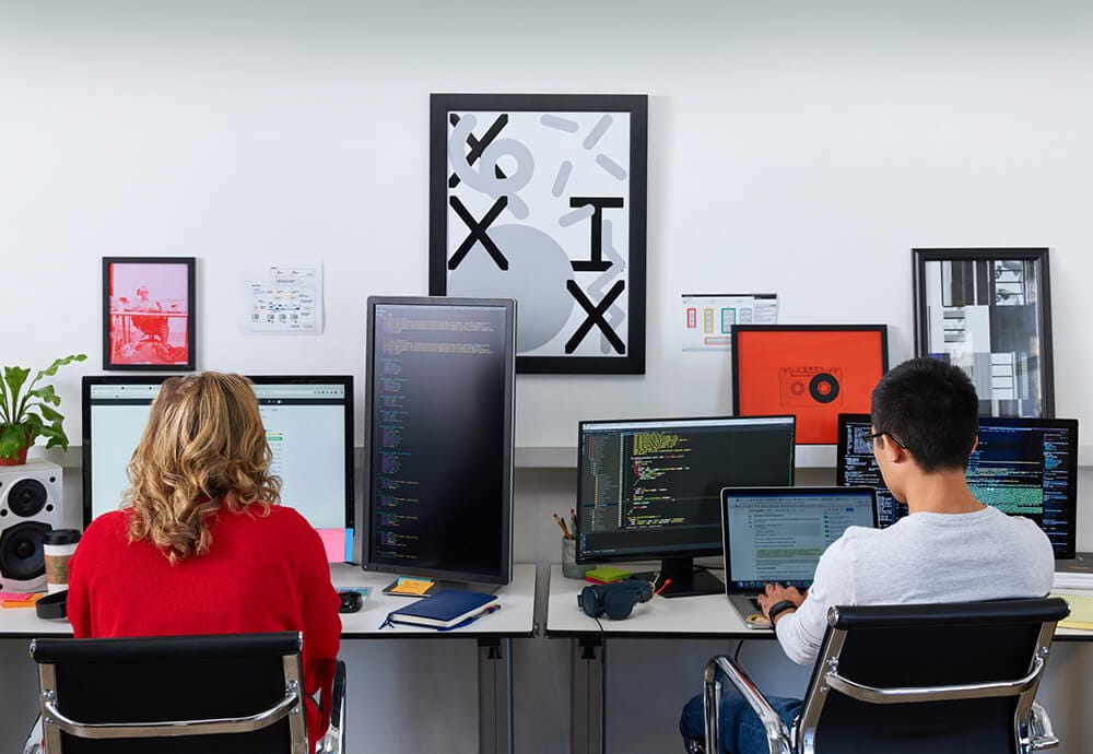 A woman and a man sit in an office surrounded by many computer screens to represent dedicated server strategy