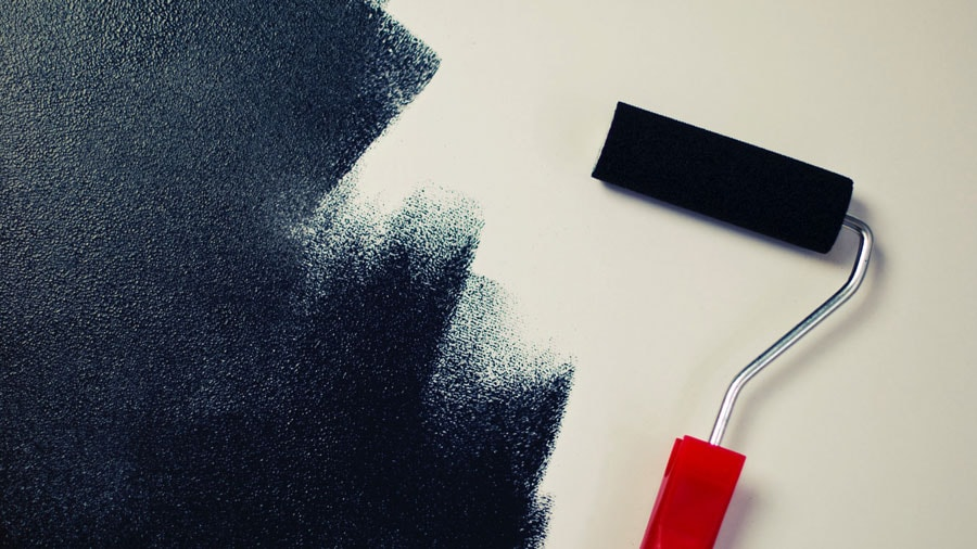 paint roller with black paint on interior wall