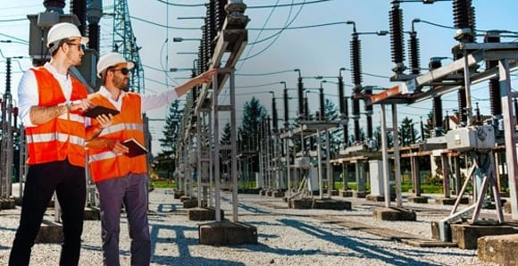 Two workers at an electrical substation