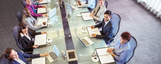 group of development and business professionals seated at a conference table gathering requirements for an application development project