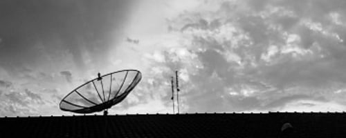 a satellite dish in contrast with clouds in a sky
