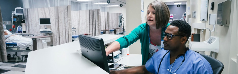A woman pointing to a computer screen to show something to a male nurse that is using the computer on a hospital computer